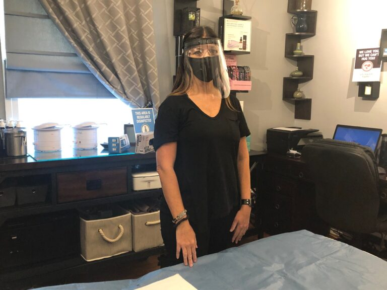 Aesthetician Jen Allegretti wears the face mask and shield she will use while working with clients. (Cris Barrish/WHYY)