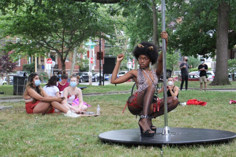 A dancer known by the professional name Tabz poses with a dance pole at Malcolm X Park. She is a leader of the group Stiletto, which held an event in the park to advocate for better working conditions for dancers and sex workers. (Emma Lee/WHYY)