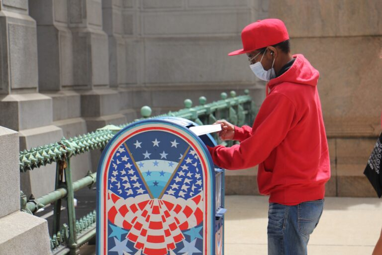 Odell Griffin places his mail-in ballot in a box outside City Hall.