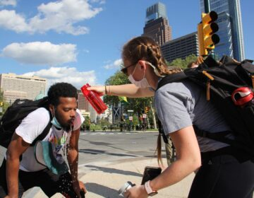 Protesters help each other after being tear gassed on the Ben Franklin Parkway. (Emma Lee/WHYY)