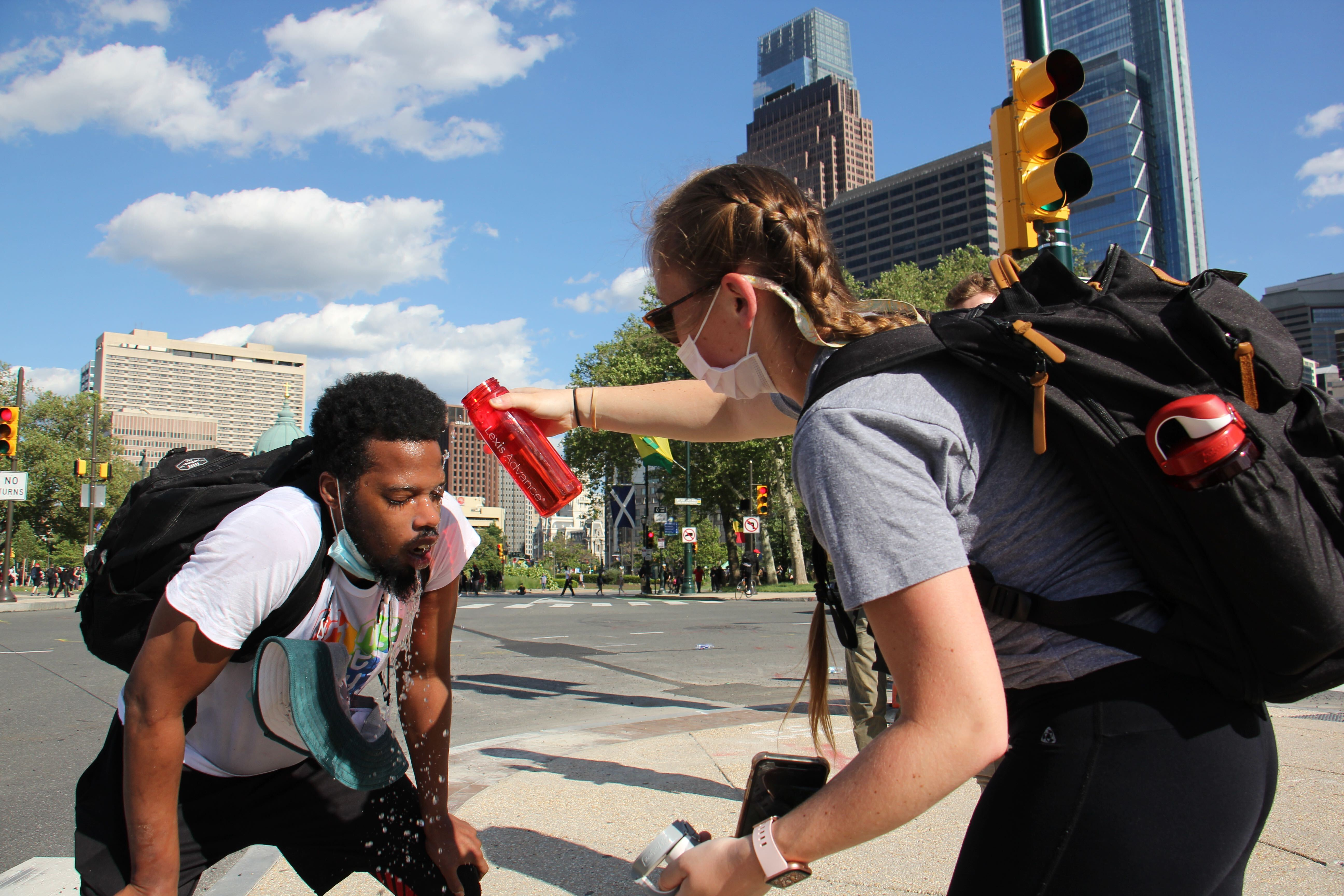 Protesters help each other after being tear-gassed on the Ben Franklin Parkway
