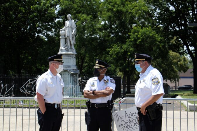 In mid-June, Philadelphia police maintained a presence at the statue of Christopher Columbus at Broad and Oregon in South Philadelphia. Some Italian Americans who see the statue as part of their heritage have turned out to guard the statue, raising the possibility of conflict with those who see it as a symbol of genocide. (Emma Lee/WHYY)