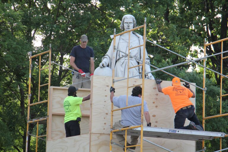 Workers box up the statue of Christopher Columbus in Marconi Plaza. (Emma Lee/WHYY)