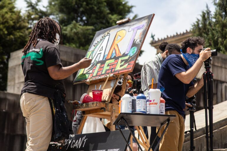 Artist Keisha Whatley paints on the steps of the Art Museum at a rally demanding funding for the arts in Philadelphia. (Kimberly Paynter/WHYY)