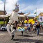 Samantha Rise leads a march demanding arts funding in a giant unicorn puppet