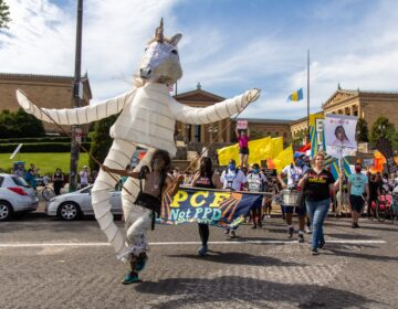 Samantha Rise, program director of Girls Rock Philly, leads a march demanding arts funding in a giant unicorn puppet