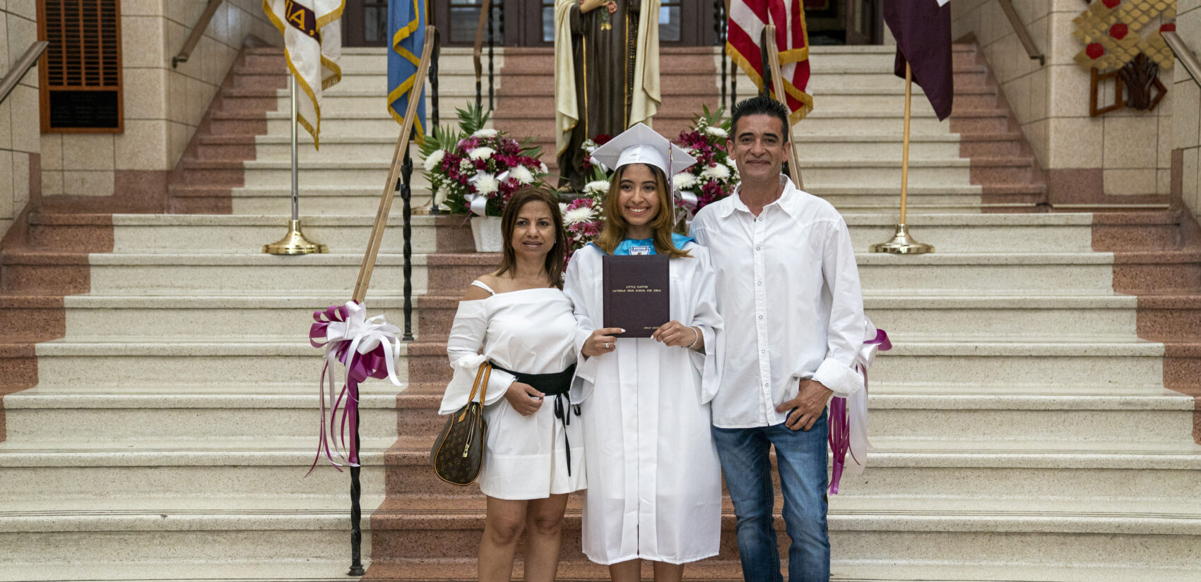 Ashley Acevedo with her parents Elena and Johnny on graduation day inside Little Flower Catholic School for Girls. (Jessica Kourkounis for Keystone Crossroads)