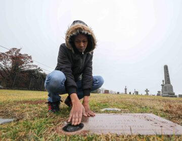 Keandra McDole kneels over the grave of her Jeremy McDole, who was shot to death by police on Tulip Street in 2015. (Saquan Stimpson for WHYY)