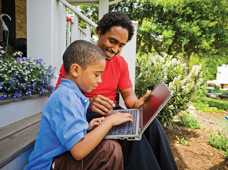 A son and father learn together on the computer while sitting on their porch