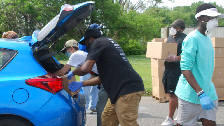 Volunteers load food boxes into cars during a food distribution by the Food Bank of South Jersey in Riverside, Burlington County on June 6. (Jon Hurdle/NJ Spotlight)