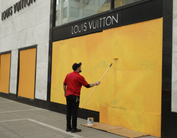 A worker paints over a Louis Vuitton storefront boarded up due to the coronavirus outbreak on March 30 in San Francisco.