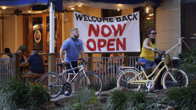 Visitors to the River Walk pass a restaurant that has reopened in San Antonio, Texas, on May 27. Texas continues to reopen in the wake of the COVID-19 pandemic.