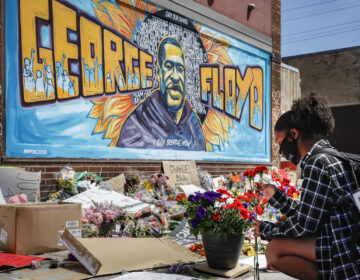 Malaysia Hammond places flowers at a memorial mural for George Floyd in Minneapolis on Sunday. Police brutality has sparked days of civil unrest. But the sparks have landed in a tinderbox built over decades of economic inequality, now exacerbated by the coronavirus pandemic.