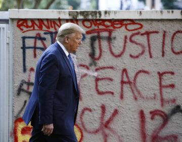 President Trump walks past protest graffiti in Lafayette Park