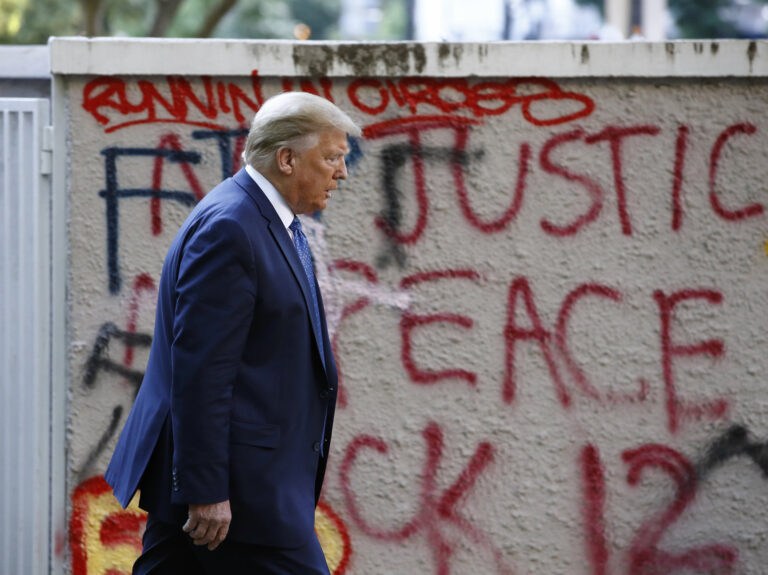 President Trump walks past protest graffiti in Lafayette Park