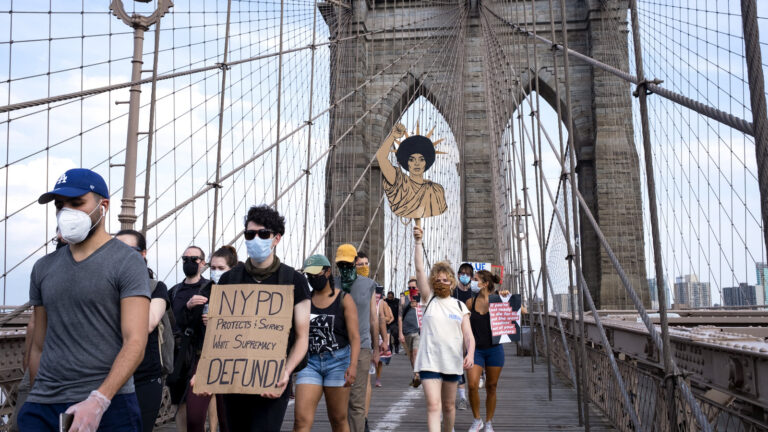 Protesters and activists walk across the Brooklyn Bridge Saturday in New York. Cities saw some of their biggest gatherings of the past two weeks on Saturday.
