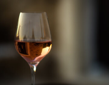 Picture in low key of glass of rose wine with reflection of old stone traditional provencal house in it. Rose wine in Provence, France. Light alcoholic drink.