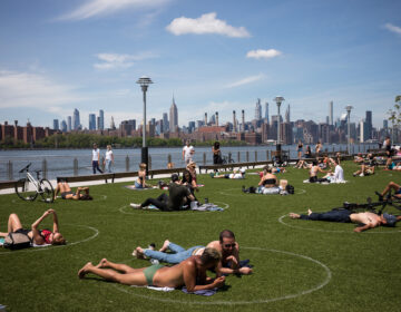 People rest inside social distancing markers at Domino Park in the Brooklyn borough of New York in late May. Stay-at-home orders in New York helped to lower the state's