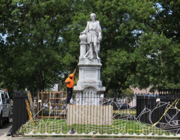 A worker measures the Christopher Columbus statue at Marconi Plaza