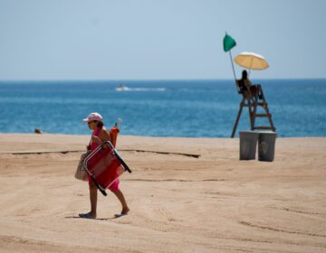 A woman walks past a lifeguard on a beach in Lloret de Mar this week, as beaches in Spain reopen following a lockdown to stop the spread of the coronavirus. The EU is now considering which countries should be allowed to send tourists to its member nations.