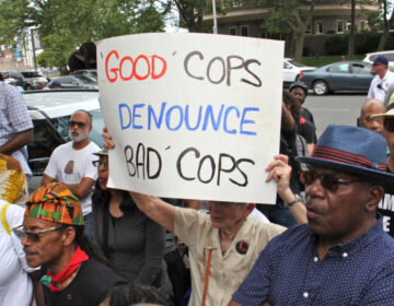 Protesters rallied outside the Philly police headquarters to demand the firing of officers identified in the Facebook database. (Emma Lee/WHYY)