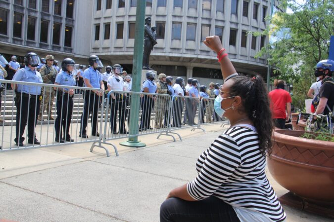 A protester kneels in front of Philadelphia police headquarters