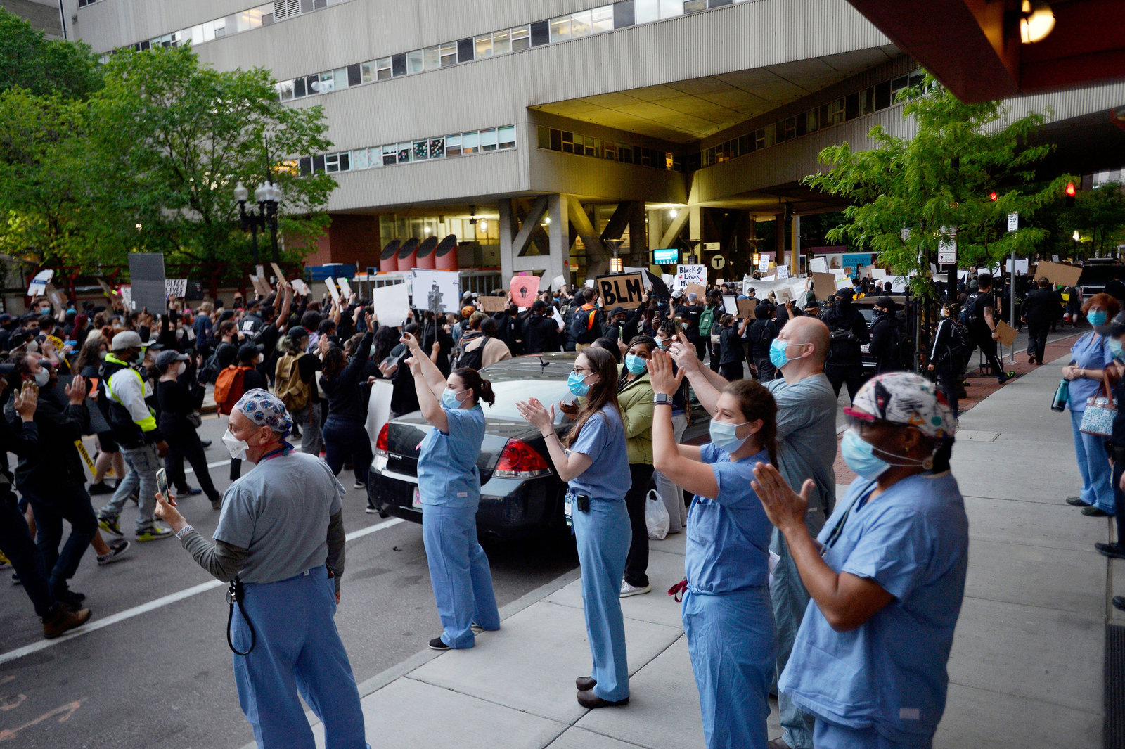 Medical workers applaud protesters outside a hospital during a demonstration over the death of George Floyd in Boston on Sunday.