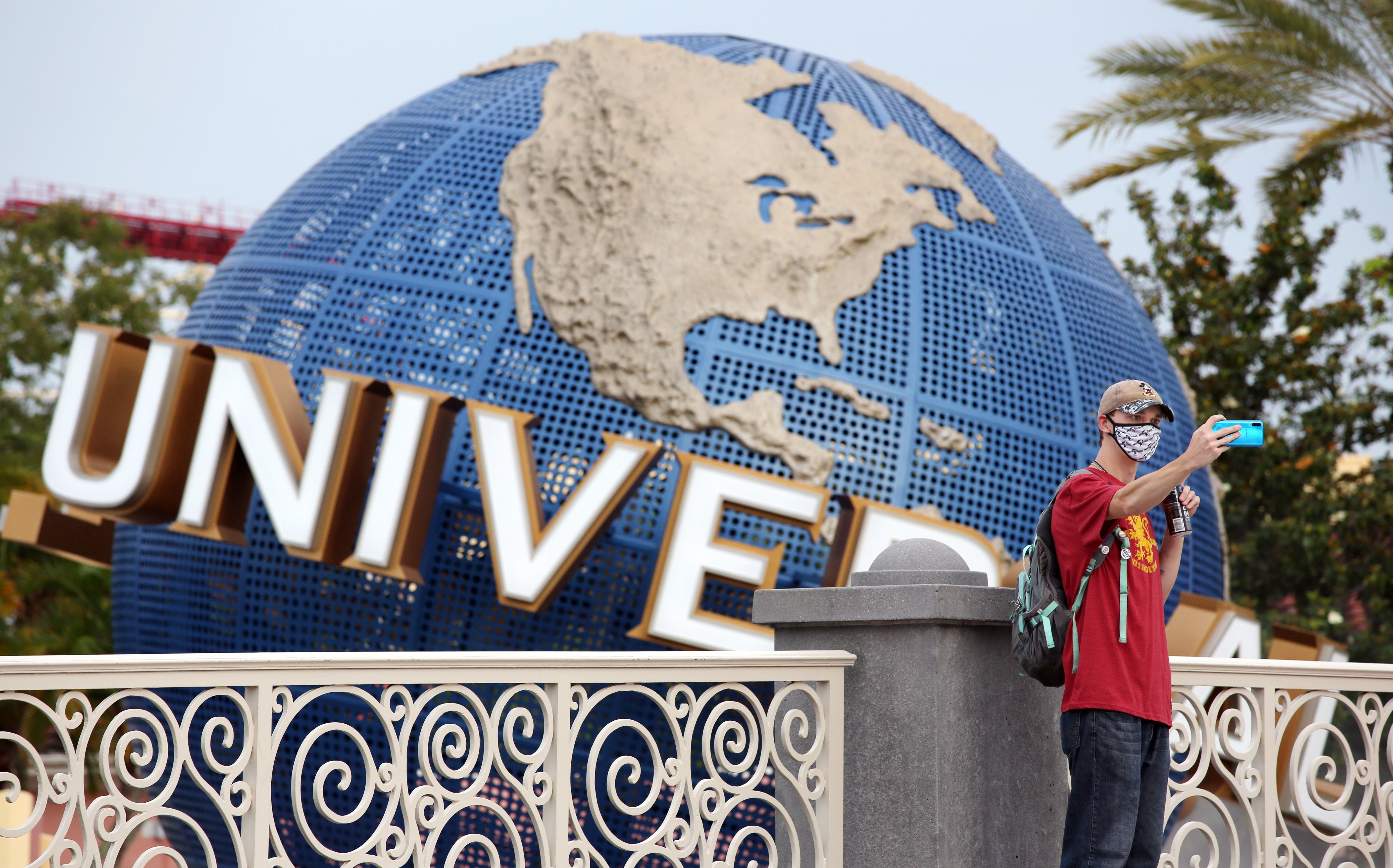 A visitor takes a selfie at Universal Studios theme park on June 5, the first day of the park's reopening during the coronavirus pandemic in Orlando, Fla.