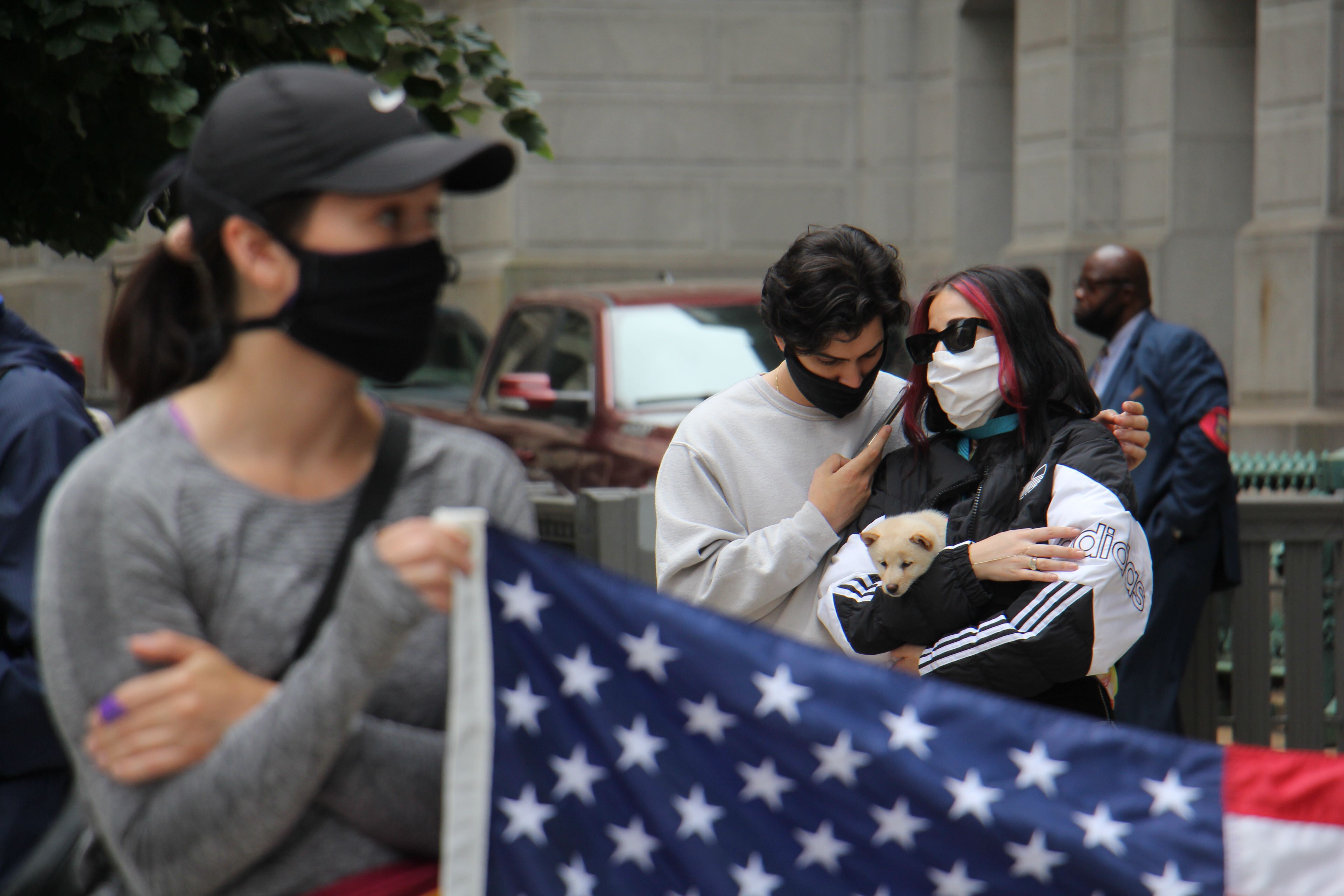 Cameron and Nina Fatholahi of Philadelphia listen to Joe Biden's speech outside City Hall, while Nina cradles an 8-week-old puppy, Penny Lane.