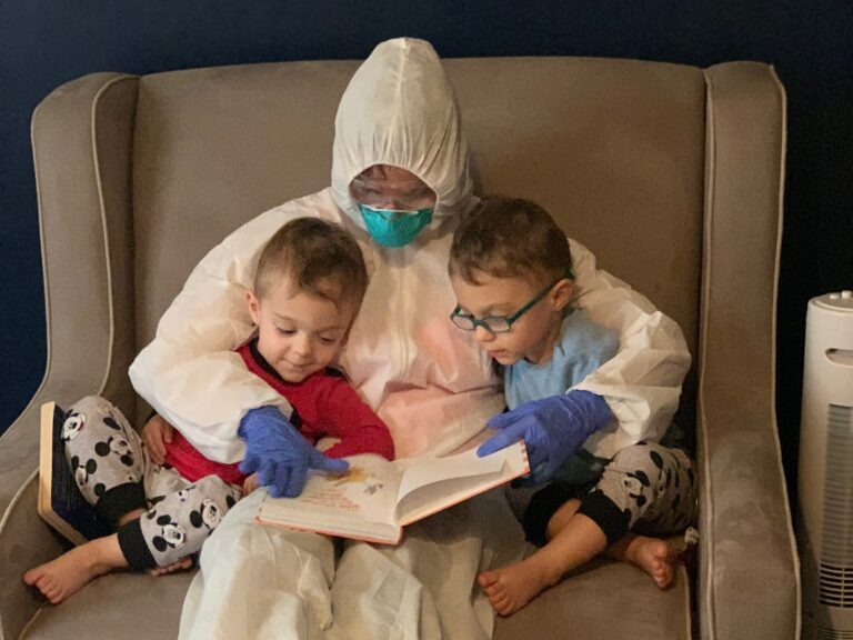 Dr. Lauren Jenkins reads to her twin sons, Pierce and Ashton, while wearing her