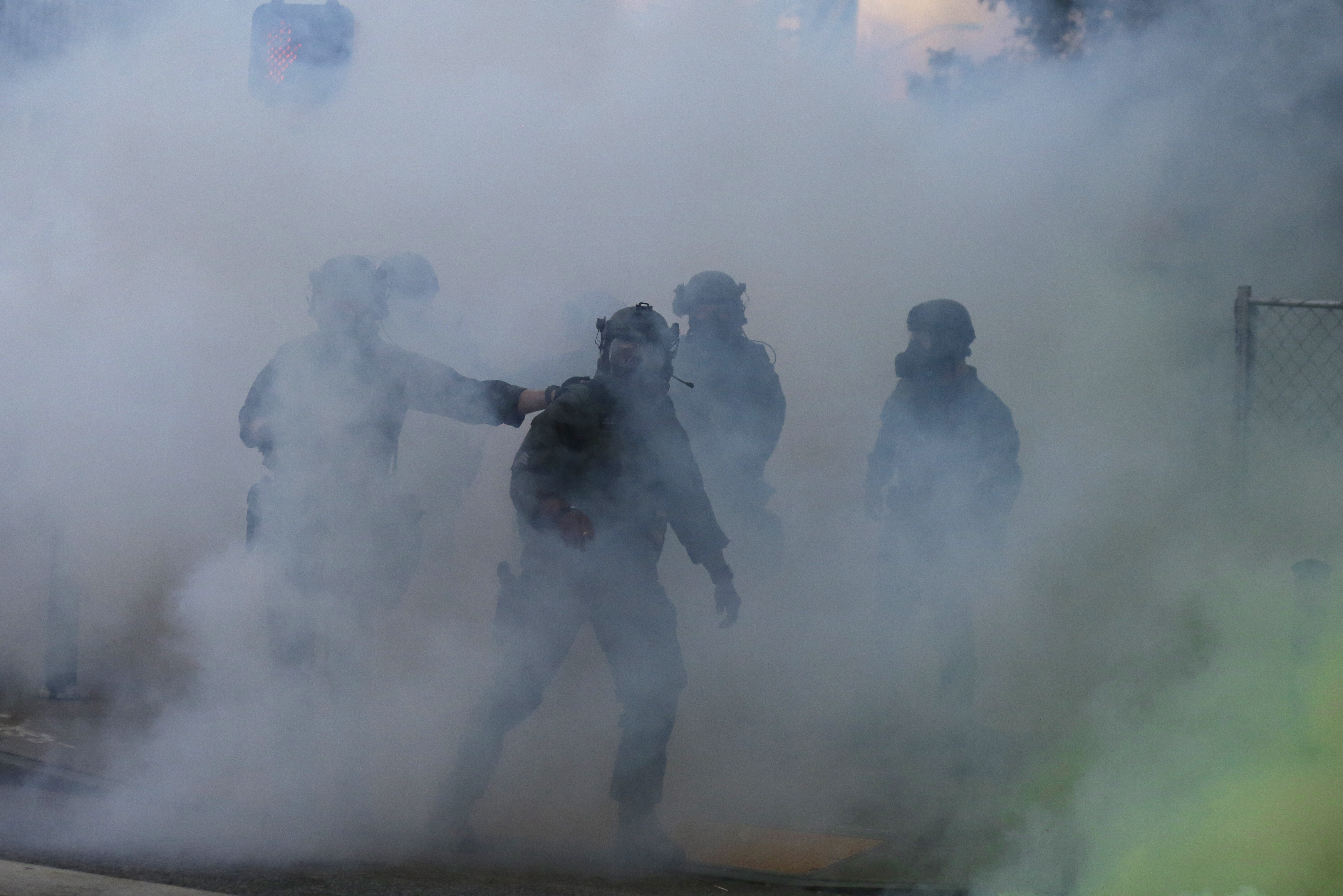 Police move through tear gas as demonstrators march on Sunday in Atlanta.