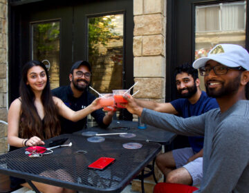 Rayyan Aziz (front left), Joel James (back left), Ravi Patel (back right) and Sean Shaji (front right) toast with margaritas at Set NoLibs outdoor seating. Today is the first day outdoor dining is allowed since coronavirus shutdowns. (Kimberly Paynter/WHYY)