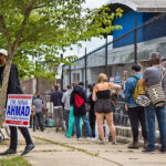 Voters wait in a socially distanced line outside their polling place