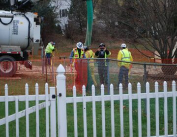 In this May 2018 photo, workers and contractors for Sunoco Pipeline investigate sink holes behind homes at Lisa Drive, West Whiteland Township, Chester County where the company has been drilling for construction of the Mariner East 2 and 2X pipelines. In the photo, a security guard is taking a picture of the reporter. (Jon Hurdle / StateImpact PA)