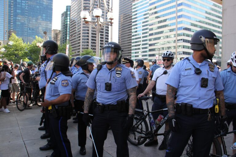 Police, some wearing body cameras, guard the Municipal Services Building during protests on May 30, 2020. (Emma Lee/WHYY)