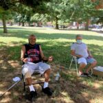 Gilberto Padilla, 78, and Carmen Román, 70, set up their chairs in the shade in Norris Square to beat the heat. (Catalina Jaramillo/WHYY)