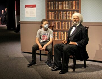 Caleb Cattell takes a seat beside a wax figure of Frederick Douglass at the Franklin Institute. The 13-year-old from Riverton, N.J., and his family were among the first wave of visitors when the Institute reopened on Wednesday. (Emma Lee/WHYY)