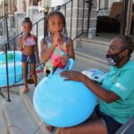 Taylor Corbin, 4, (center) helps block captain Roslyn Myers inflate a hopper ball for a Playstreets event in the 5800 block of Delancey Street. (Emma Lee/WHYY)