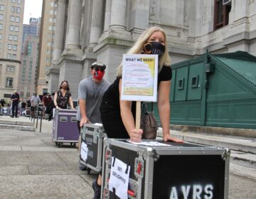 Members of the Live Events Coalition push roadie cases around City Hall to draw attention to their plight. (Emma Lee/WHYY)