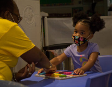 Kimrenee Patterson works on a puzzle, with Peyton, 2, at Patterson's daycare in Philadelphia. (Kimberly Paynter/WHYY)