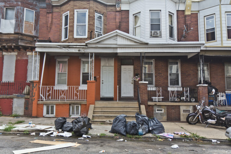 Bagged up trash sit outside Philly homes