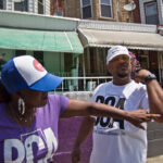Saj Blackwell points to Thomas Blackwell's scar, where he was nicked with a rubber bullet the night of protests and looting on 52nd Street in Philadelphia. (Kimberly Paynter/WHYY)