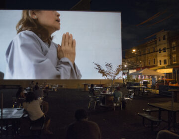 A woman holds her hands in a prayer position in the video by Kevin Nguyen projected during the 'Cleanse' exhibit in the Italian Market on July 11, 2020. (Photo by Lori Waselchuk)