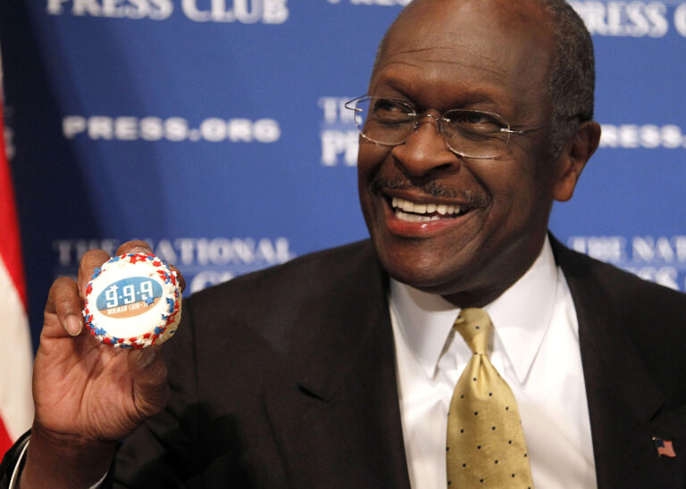 In this Oct. 31, 2011 file photo, then-Republican presidential candidate Herman Cain holds up a muffin that has his catch-phrase 9-9-9 tax plan printed on it  before speaking at the National Press Club in Washington. (AP Photo/Pablo Martinez Monsivais)