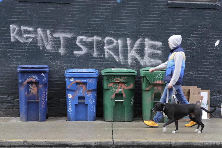 A pedestrian walks past graffiti that reads