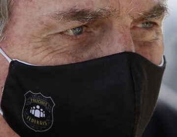 FILE - In this May 26, 2020 file photo, Brazil's President Jair Bolsonaro, wearing a face mask with a logo of the Federal Police, leaves his official residence of Alvorada Palace in Brasilia, Brazil.  (AP Photo/Eraldo Peres, FIle)