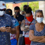 People waiting in line to enter a grocery store wear COVID-19 protective masks