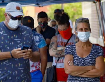 People waiting in line to enter a grocery store wear COVID-19 protective masks, Friday, July 3, 2020, in McCandless, Pa. Gov. Tom Wolf's more expansive mask order issued this week as the coronavirus shows new signs of life in Pennsylvania and the July Fourth holiday starts has been met with hostility from Republicans objecting to the Democrat's use of power or even to wearing a mask itself. (AP Photo/Keith Srakocic)