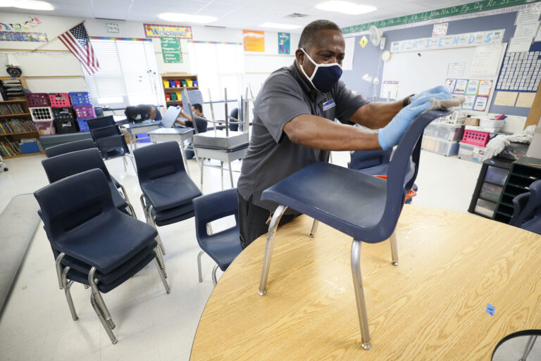Custodian Tracy Harris cleans chairs in a classroom at Brubaker Elementary School, Wednesday, July 8, 2020, in Des Moines, Iowa. (AP Photo/Charlie Neibergall)