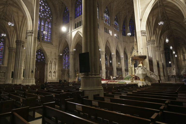 In this Sunday, April 12, 2020 file photo, Archbishop Timothy Dolan, right, delivers his homily over mostly empty pews as he leads an Easter Mass at St. Patrick's Cathedral in New York. (AP Photo/Seth Wenig)
